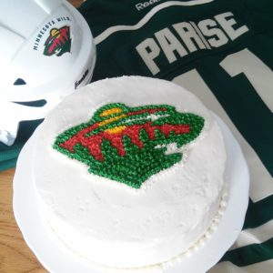Vanilla cake with dyed green and red layers inside. Printed the Wild logo onto paper, then piped over wax paper with the paper underneath, freeze, transfer to cake, and touch up.